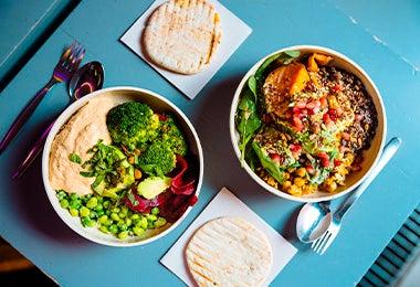 Mesa con dos platos de comida con vegetales