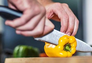 Pimiento amarillo siendo cortado para rellenar en un asado vegetariano