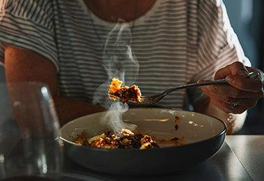 Mujer comiendo pasta de noche