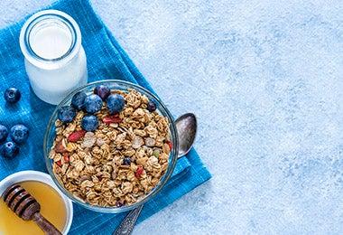 Bowl con granola, fruta, leche y miel en desayuno continental