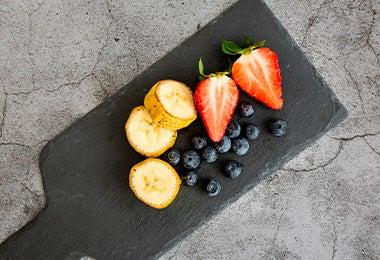 Tabla con frutilla, arándanos y banana en desayuno continental