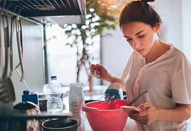 Mujer preparando galletitas fáciles mirando receta