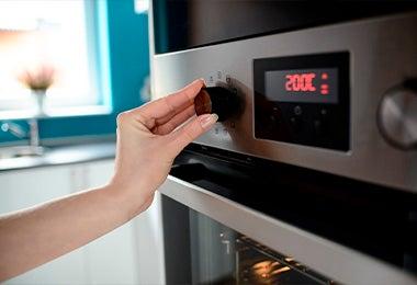 Mujer ajustado temperatura en horno para hacer galletitas fáciles