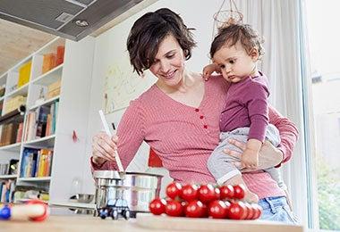 Mujer cocinando con una olla de acero inoxidable junto a su hija