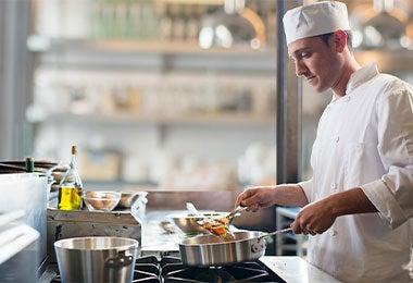 Chef usando una sartén de acero inoxidable.