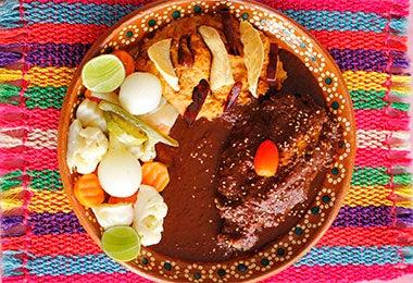 Un plato de mole con pollo y verduras