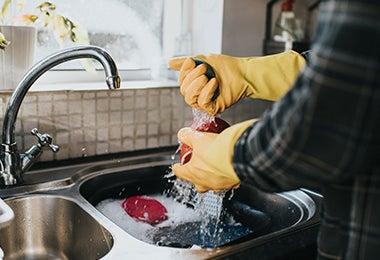 Hombre lavando en casa olla quemada