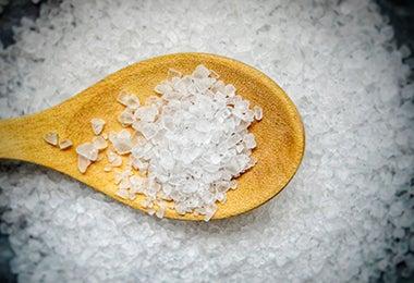 Cuchara de palo con sal gruesa para limpiar olla quemada